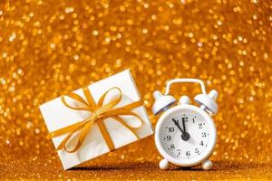 Christmas gift and alarm clock on shining gold background. photo