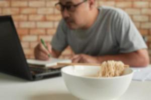 Male works with a laptop and eats instant noodles during lunch breaks. photo