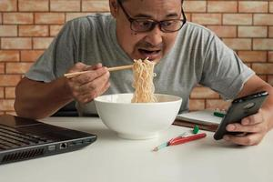 Asian male workers are busy, eating instant noodles during lunchtime. photo