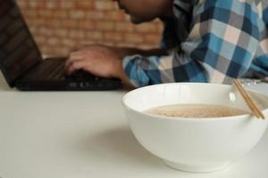 Asian male worker hastily eats instant noodles at busy overtime work. photo