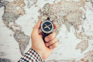 Man hold compass to check the direction with blurred map background photo