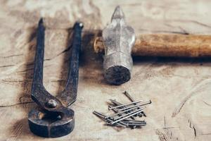 Old rusty pincers, nails and hammer on a wooden background photo