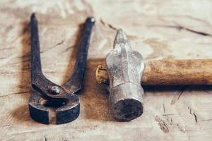 Old rusty pincers and hammer on a wooden background photo