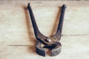 Old rusty pincers on a wooden background photo
