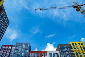 Building crane on the background of colored buildings photo