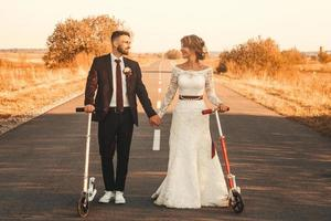 wedding couple riding a on scooters along road outside city at sunset photo