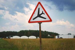 Señal de carretera con triángulo y aterrizaje de avión de pie en el campo en el cielo foto