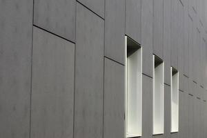 Window openings on the sides of a modern gray building photo