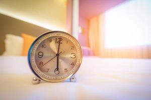Despertador en la cama por la mañana con luz solar. foto