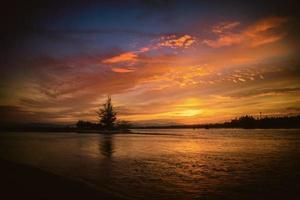 hermoso paisaje de puesta de sol sobre el mar con silueta de árbol foto