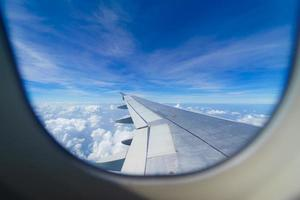 Wing of an airplane flying above the clouds look from cabin window. photo