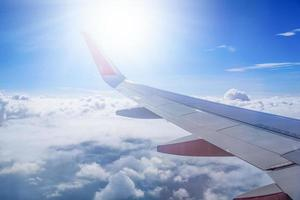 Wing of airplane flying above the clouds in the blue sky background photo