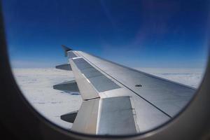 ala de un avión que vuela por encima de las nubes mira desde la ventana de la cabina. foto