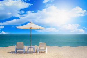 Dos sillas de playa y sombrilla blanca con fondo de cielo azul foto
