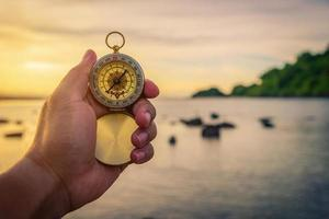 Compass in the hand on the nature background. photo