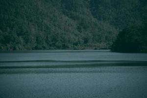 Fondo de lago y montaña en Tailandia. tono oscuro foto