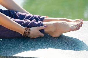 Close up female hands holding feet sitting pose photo