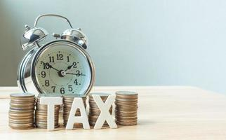 Concept tax time season and alarm clock with coins stack photo