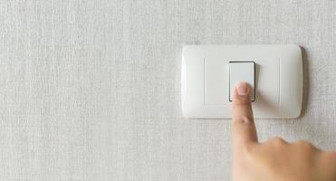 Concept save energy. Hand turning off switch photo