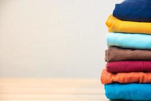 Stack of colorful clothes on wood table photo