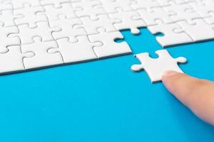 Hand putting piece of white jigsaw puzzle on blue background photo