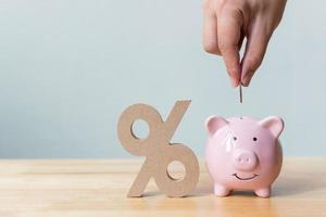 Hand putting money coin in piggy bank with percentage sign symbol photo