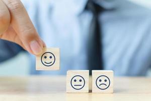 mano de un empresario elige una cara sonriente foto