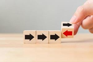 Hand flip over wooden cube block with red arrow photo