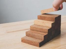 Hand arranging wood block stacking as step stair photo