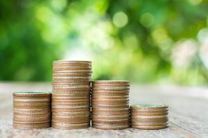 Pila de monedas en la mesa de madera con fondo verde borroso foto
