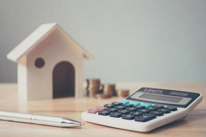 Calculator with wooden house and coins stack and pen photo