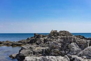 Rocks and stones on the background of the sea under the blue sky. photo