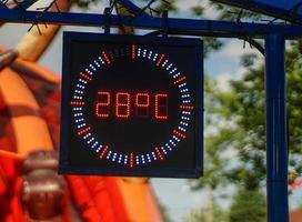 Pantalla de temperatura en el parque infantil en un caluroso día de verano. foto