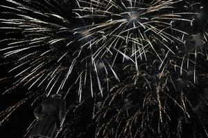 blurred festive dark background with bright sparks of the fireworks photo