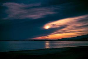 dramatic sunset on the background of the sea and coastline photo