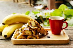 Close up of French toast with banana fruits and Red coffee cups photo