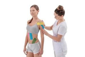 Physiotherapist applying kinesio tape on female patients shoulder photo