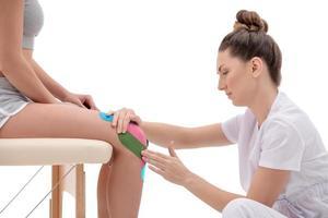 Técnicas de kinesio terapia realizadas por fisioterapeuta en rodilla. foto