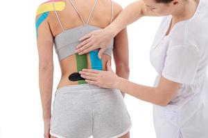 Physical therapist applying kinesio tape on female patient's back photo
