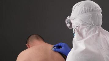 Doctor examine man symptom of coronavirus, doctor listens breathing photo