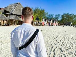 Male tourist walking along the beach in Zanzibar photo