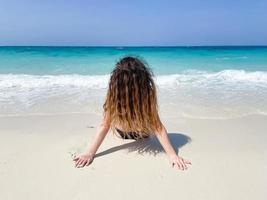 Woman in a tropical beach or back view of a girl sitting on the ocean photo