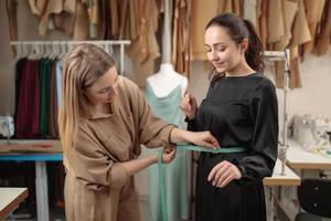 Tailor or fashion designer measuring a woman model at workshop studio photo