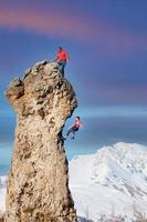 un escalador en la cima hace que su compañero baje por la cuerda foto