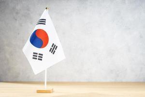 Bandera de mesa de Corea del Sur en la pared con textura blanca. copia espacio foto