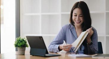 mano de mujer asiática de negocios tomando notas con varios elementos colocados foto