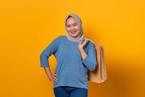 Cheerful Asian woman holding shopping bag over yellow background photo