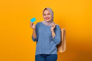 Cheerful Asian woman holding shopping bag and showing credit card photo
