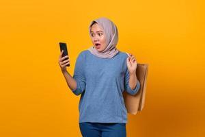 Conmocionada mujer asiática sosteniendo teléfono y bolsa de compras foto