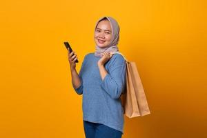 Portrait of cheerful Asian woman holding phone and shopping bag photo